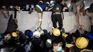 Pro-democracy protesters climb a wall as police officers disperse them outside the Legislative Council building after clashes with pro-democracy activists on 19 November 2014 in Hong Kong.