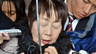 In this photo taken in March, Chisako Kakehi is surrounded by reporters in Sakai, western Japan.