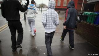 Teenagers playing football in street