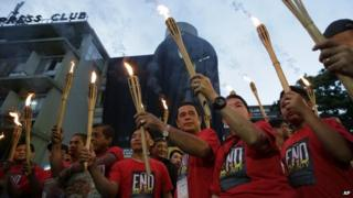 Journalists in Manila carry torches ahead of commemorations of the Maguindanao massacre. Photo: 21 November 2014