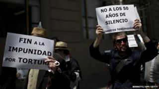Members of human rights organizations protest in front of the presidential Palace La Moneda in Santiago, on 3 October, 2014