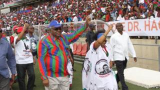 Namibian president Hifikepunye Pohamba, centre left, and his first lady, Penehupifo Pohamba, centre right, arrive at the Sam Nujoma Stadium in Windhoek, Namibia for an election rally