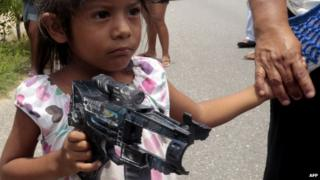 A Mexican girl holds a toy gun in south-western Guerrero state
