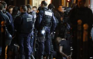 One of the two alleged robbers who attempted to rob a Cartier jewellery store on the Champs-Elysees sits on the ground after surrendering to French police forces in Paris 25 November 2014