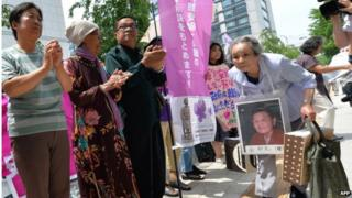 Former 'comfort women' and their relatives gather to stage a standing demonstration near the Diet, or parliament, in Tokyo on 2 June 2014 to demand that Japan formally atone for forcing women into sexual slavery in its wartime military brothels.