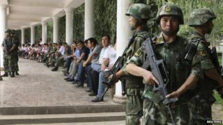 "Paramilitary policemen stand guard during a ceremony to award those who the authorities say participated in ""the crackdown of violence and terrorists activities"" in Hotan, Xinjiang Uighur Autonomous Region 3 August 2014"