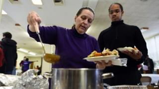 A woman gets a Thanksgiving meal at a church in Ferguson