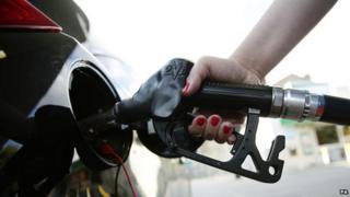 Hand on petrol pump filling up car