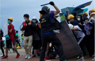 A policeman clashes with pro-democracy protesters during an operation to clear an occupied road near the government headquarters in the Admiralty district of Hong Kong early on 1 December 2014