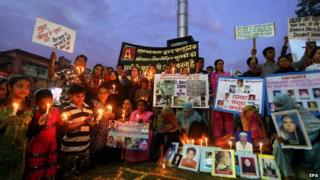 Survivors and relatives of Bhopal gas victims hold photos of the victims during a candle light vigil on the eve of the 30th anniversary of the tragedy on 1 December 2014.