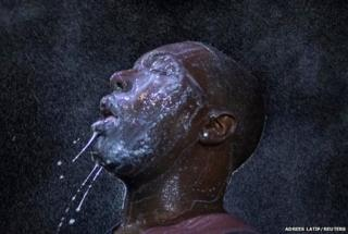 A man is doused with milk and sprayed with mist after being hit by an eye irritant from security forces in Ferguson