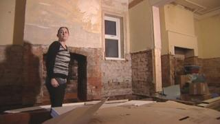 Lisa Moss standing in a derelict living and dining space in her house