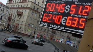 A board showing the rouble exchange rate above a street