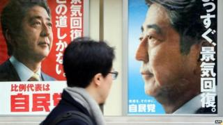 A man walks past posters of Japanese Prime Minister and ruling Liberal Democratic Party (LDP) leader Shinzo Abe displayed at the LDP headquarters in Tokyo on 4 December 2014
