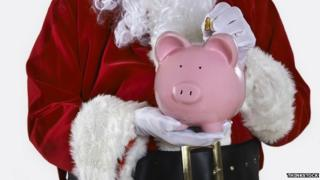 Father Christmas holding a piggy bank
