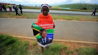 A young girl waits for the funeral cortege of former South African president Nelson Mandela as it passes through Qunu on its way to his family's rural home on 14 December 2013 in Qunu, South Africa