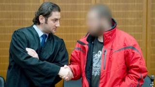 Berisha, to the right, greets his lawyer, Mutlu Guenal, at the court in Frankfurt