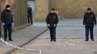 Police officers search an area where Joel Adesina was stabbed