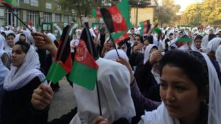 Rita Faizi (front) and her classmates hold flags