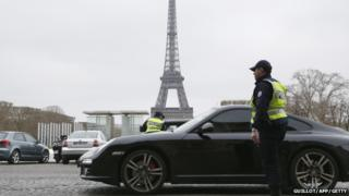 Police officers control cars in front of the Eiffel Tower, in Paris, on March 17, 2014