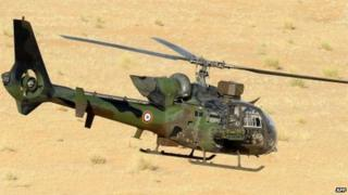 A French army helicopter Gazelle flies over the desert during the Hydra Operation on 29 October 2013 near the village of Bamba between Timbuktu and Gao, northern Mali