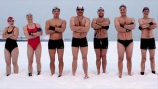 Swimmers stand in the snow on Brighton beach