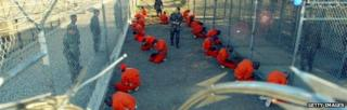 U.S. Military Police guard Taliban and al Qaeda detainees in orange jumpsuits January 11, 2002