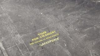 "Greenpeace activists stand next to massive letters delivering the message ""Time for Change: The Future is Renewable,"" next to the hummingbird geoglyph in Nazca on 8 December, 2014"