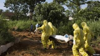 A burial team wearing protective clothing prepare the body of a person suspected to have died of the Ebola virus for interment in Sierra Leone