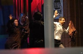 Hostages run from the cafe towards police in Sydney, 15 December