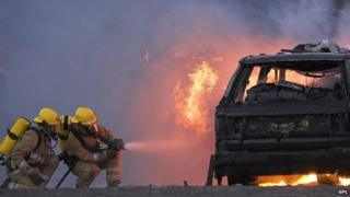 Firefighters tackling a car blaze