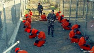 Taliban prisoners in orange jumpsuits kneel outside at the Guantanamo detention facility.