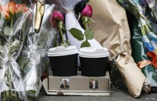 Coffee cups with one rose placed in each, with images of the two victims who died in the cafe siege, lawyer Katrina Dawson (L) and Lindt store manager Tori Johnson, at a makeshift memorial in Sydney, 17 December 2014.