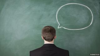 Man with back to camera next to blackboard with speech bubble chalked on