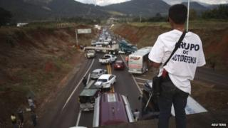 A vigilante stands guard on a bridge during a blockade on a highway near the town of Uruapanon 14 December, 2014.