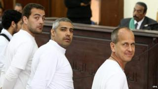"""Australian journalist Peter Greste (R), Canadian-Egyptian journalist Mohammed Fahmy (C) and journalist Baher Mahmoud (L) standing in front of the judge""""s bench during their trial on 31 March 2014"""