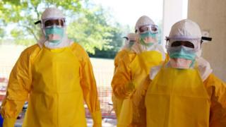 Staff in personal protective equipment to shield against Ebola