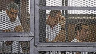 from left, Mohammed Fahmy, Canadian-Egyptian acting bureau chief of al-Jazeera, Australian correspondent Peter Greste, and Egyptian producer Baher Mohamed appear in a defendants' cage along with several other defendants during their trial on terror charges at a courtroom in Cairo. The United States and other countries on Wednesday, 5 November 2014