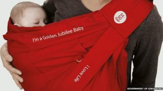 """A baby in a sling printed with """"I'm a Golden Jubilee baby"""""""