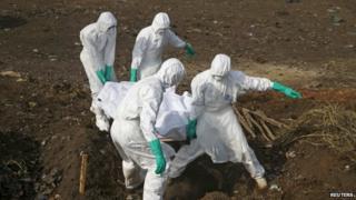 Health workers bury a body in Sierra Leone