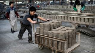 A Chinese worker pushes a cart full of clay in Dehua, Fujian Province, China.