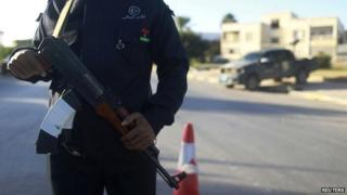 A security officer stands with his weapon on a road leading to a police station in Benghazi - 4 December 2014