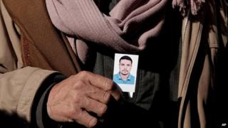 Coptic Christian Samir Mujeed holds a photo of his son, Girgis Samir, who was abducted in Libya - 5 January 2015