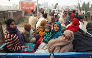 Indian villagers sit in the back of a vehicle as they flee their homes fearing firing from the Pakistan side of the border at Bainglad village in Samba sector, about 52 Kilometers from Jammu, India, Saturday, Jan. 3, 2015.