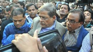 Fakhrul Islam Alamgir (centre), secretary general of the Bangladesh Nationalist Party (BNP), is escorted following his arrest in Dhaka (06 January 2015)