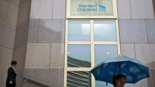 People walk down a stairway from the Standard Chartered bank headquarters building in Hong Kong on August 20, 2014.