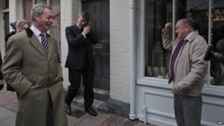 Nigel Farage walks past a supporter in Rochester, Kent