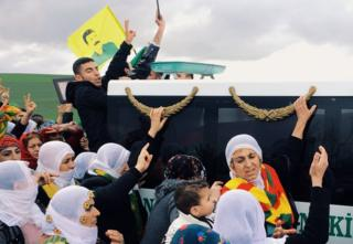 Kurdish women march alongside a convoy carrying the body of Gulsum Cam, a 24-year-old Turkish Kurdish PKK guerrilla killed fighting Islamic State in Kobane. A flag displaying the face of imprisoned PKK leader Abdullah Ocalan flies among the crowd.