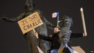 "Man holding a sign with ""Je suis Charlie"" in Paris"