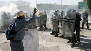 Relatives of the 43 missing Mexican students clash with police as they try to enter army facilities in Iguala on 12 January 2014